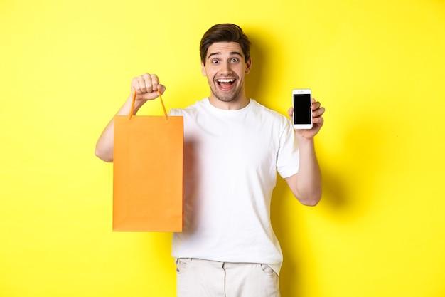 놀란 남자는 쇼핑백을 들고 스마트폰 화면, 모바일 뱅킹 및 앱 성과의 개념, 노란색 배경을 보여줍니다.