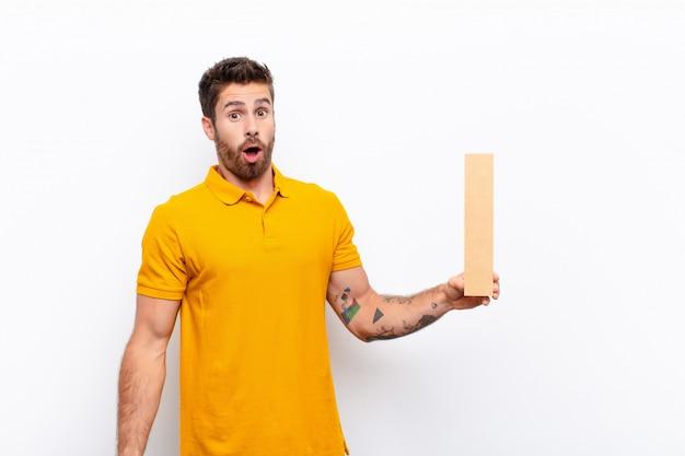 Удивленный мужчина держит букву я алфавита, чтобы сформировать слово