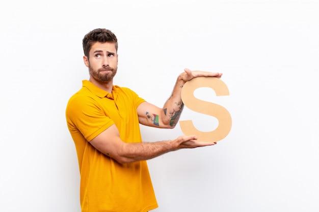 Удивленный мужчина держит букву s алфавита, чтобы сформировать слово или предложение