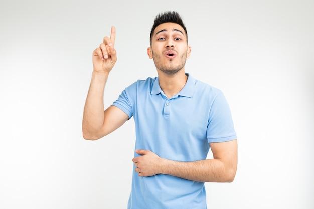 Удивленный мужчина в синей футболке предлагает идею, показывая большой палец вверх