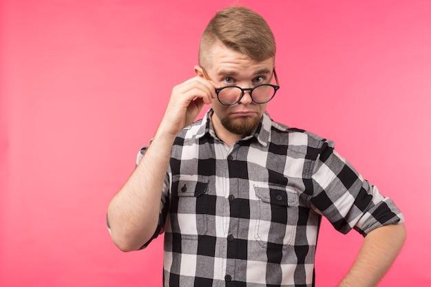 Удивленный мужчина в клетчатой рубашке снимает очки на розовой стене