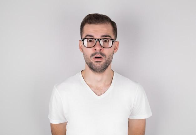灰色の背景の上に白いアンダーシャツを着て眼鏡をかけて驚いた男