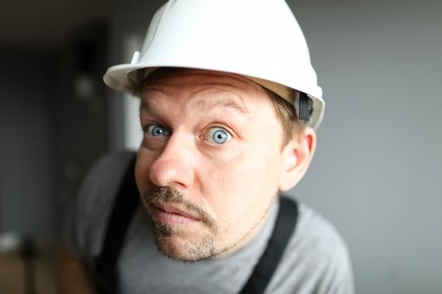 ヘルメットをかぶった驚いた男がよく見て耳を傾けます。