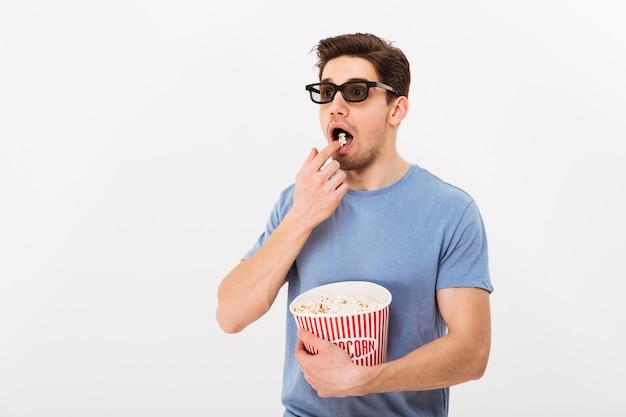 Удивленный мужчина в футболке и 3d очках ест попкорн из ведра и смотрит в сторону серой стены