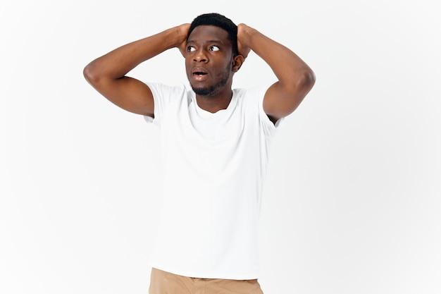 彼の頭の感情スタジオを保持している白いtシャツで驚いた男