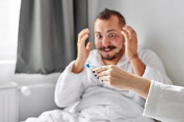 Surprised man is emotionally reacts on pregnancy, focus on hand with test
