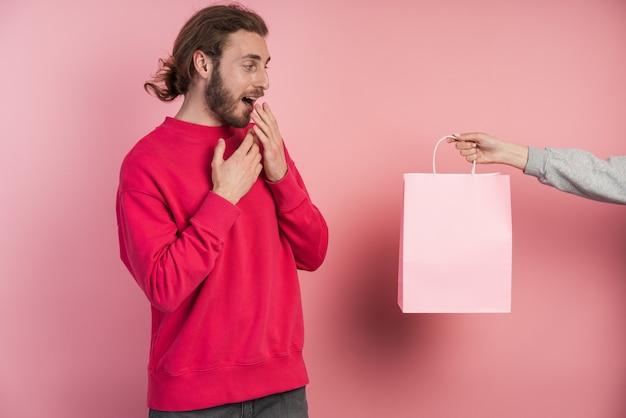 놀란 남자에게 종이, 분홍색 가방이 주어집니다. 남자에게 선물이 주어졌습니다.