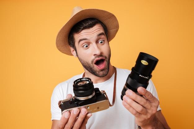 Удивленный человек, глядя на большой объектив для камеры