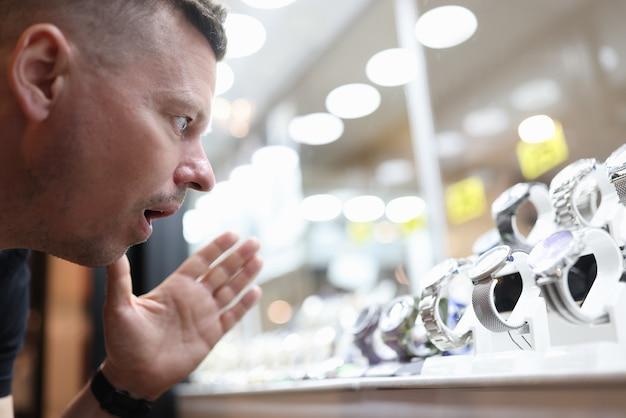 高価な時計でガラスの陳列ケースを見て驚いた男