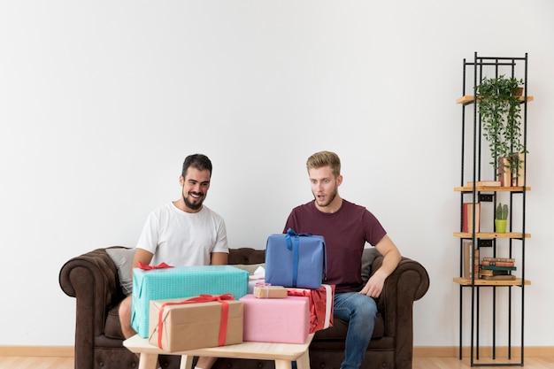 Uomo sorpreso che esamina molti contenitori di regalo variopinti che si siedono con il suo amico