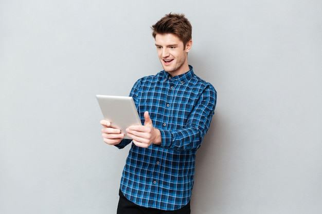 Surprised man looking at tablet computer isolated
