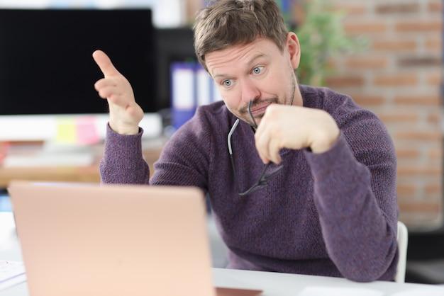 驚いた男はオフィスでノートパソコンの画面を見てください。ビジネスコンセプトの新しいアイデア