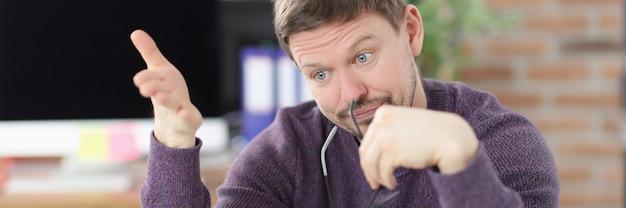 驚いた男は、ビジネスコンセプトの新しいアイデアをオフィスでノートパソコンの画面を見て