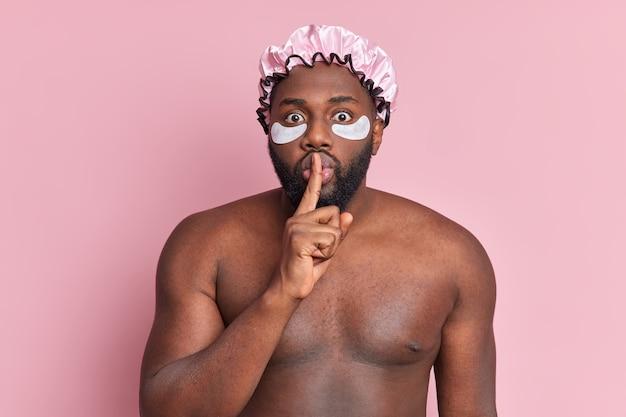 Удивленный мужчина делает жест молчания, просит не распространять слухи, носит банную шляпу, накладывает коллагеновые пластыри, чтобы уменьшить тонкую линию под глазами, позирует топлес на розовой стене