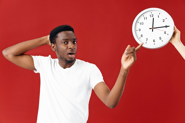 白いtシャツのトリミングされたビューで時計の横に驚いた男
