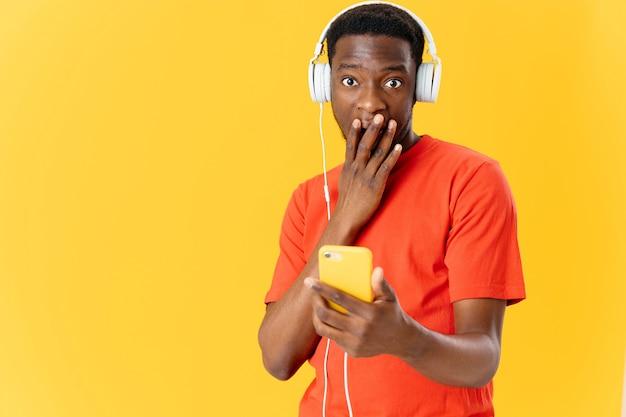 ヘッドフォンで音楽を聴いている彼の手に電話を持つアフリカの外見の驚いた男