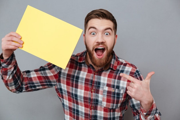 Surprised man in shirt holding blank board