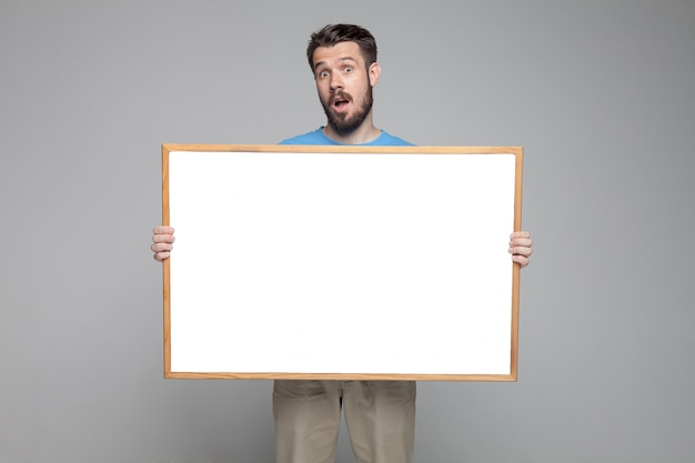 Surprised man showing empty white board