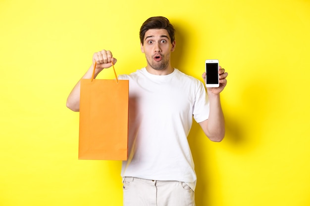 Surprised man showing mobile screen and shopping bag, standing against yellow wall