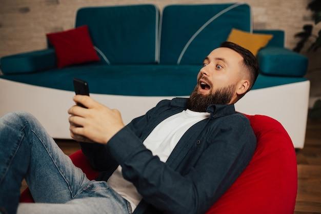 놀란 남자가 안락 의자에 앉아 스마트 폰을 들고 장치 화면을 보면 혼란스럽고 충격을 받았습니다.