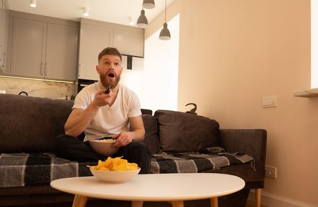 Удивленный мужчина сидит на диване и смотрит телевизор или фильм. молодой европейский парень держит пульт дистанционного управления и миску с попкорном. чаша с фишками на столе. концепция отдыха дома. интерьер однокомнатной квартиры