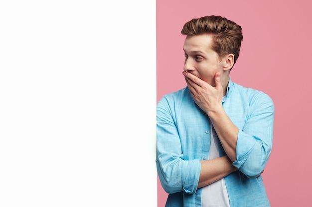 Удивленный человек, стоящий рядом с пустой белой стеной рекламного щита на розовом фоне