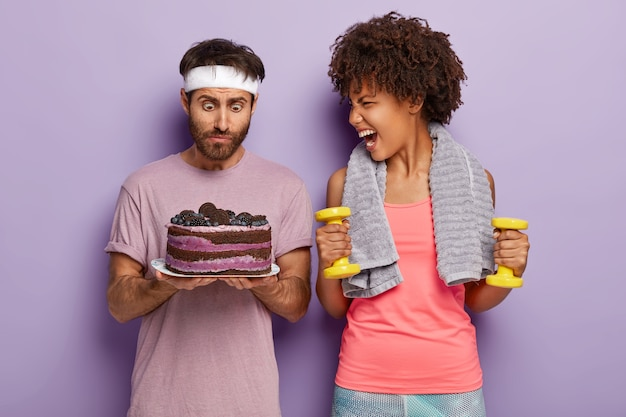 Surprised man stares at baked sweet cake, feels temptation and emotional woman shouts at him, holds yellow dumbbells