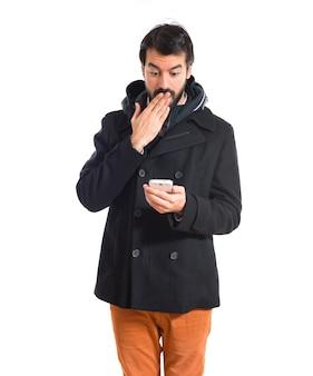 Удивленный мужчина разговаривает с мобильным