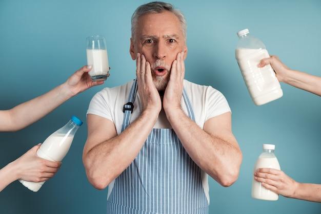 놀란 남자는 우유 병으로 둘러싸인 손으로 얼굴을 만집니다.