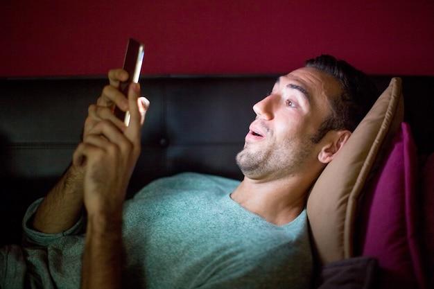 Удивленный человек с помощью смартфона на диване в ночное время