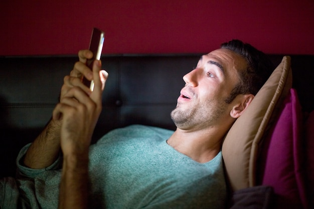 Surprised man using smartphone on sofa at night