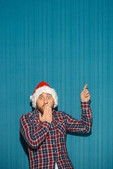 Удивленный мужчина в шляпе санта-клауса показывает что-нибудь на синем фоне