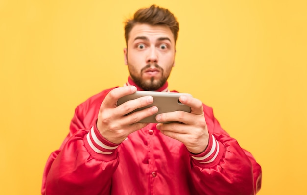 驚いた男は赤いジャケットを着て、黄色に分離された彼の手でスマートフォンを保持