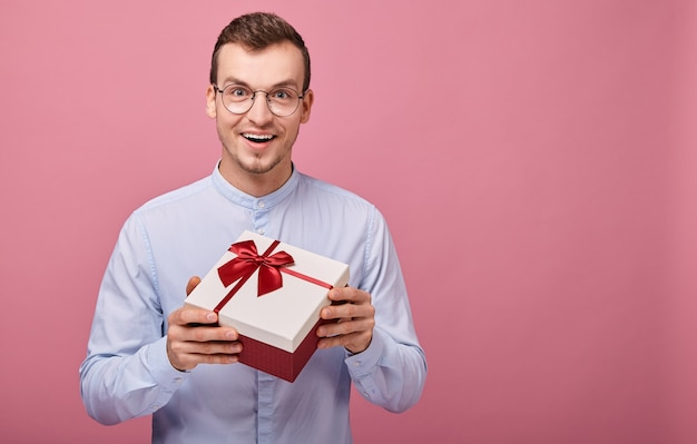 Surprised man with black glasses holds gift in box