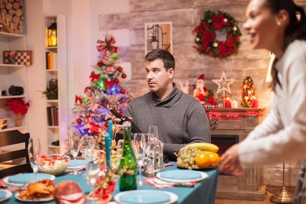 Surprised man with a bottle of wine sitting at table for christmas dinner.