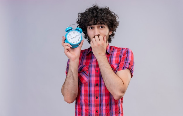 A surprised man with curly hair in checked shirt holding blue alarm clock