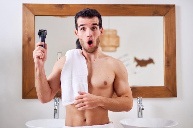 朝、お風呂の鏡の近くに立っている、肩にタオルを持った電気かみそりを持った驚いた男