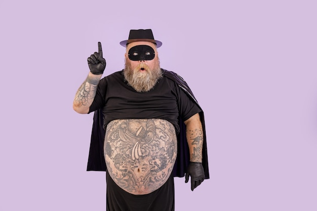 Surprised man with overweight in hero suit got idea and points up on purple background
