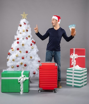 Uomo sorpreso con la valigia rossa che tiene i suoi biglietti di viaggio su grigio