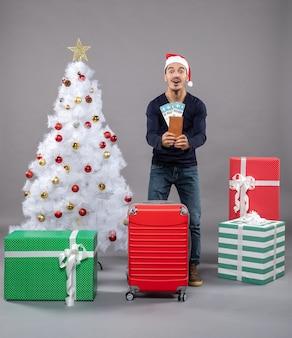 Uomo sorpreso con la valigia rossa che tiene i suoi biglietti di viaggio con entrambe le mani vicino all'albero di natale su grigio