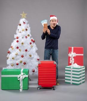 Uomo sorpreso con la valigia che tiene i suoi biglietti di viaggio con entrambe le mani su grigio