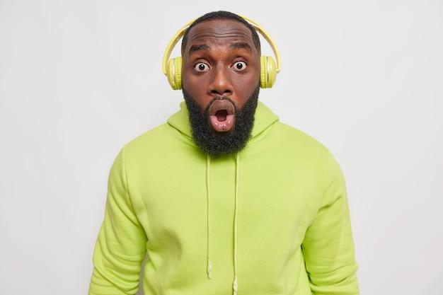 Удивленный мужчина с густой бородой смотрит на глаза запуганными глазами с удивленным выражением лица, не может поверить в шокирующие новости, носит беспроводные наушники, повседневную зеленую толстовку, изолированную на белом