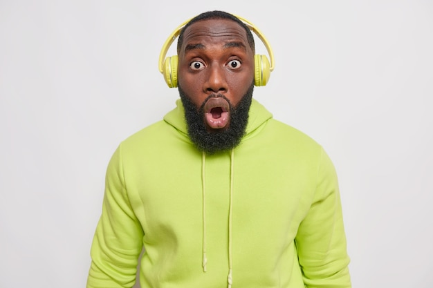 Surprised man with thick beard stares bugged eyes at front has startled expression cannot believe in shocking news wears wireless headphones casual green sweatshirt isolated on white
