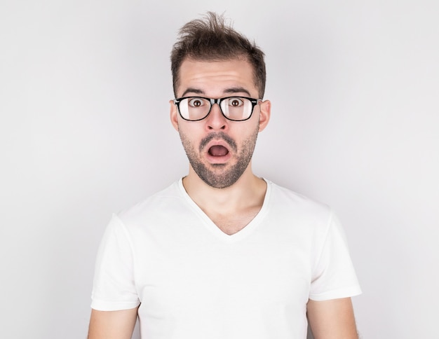 Surprised man with tousled hair wearing glasses in white t-shirt on gray wall