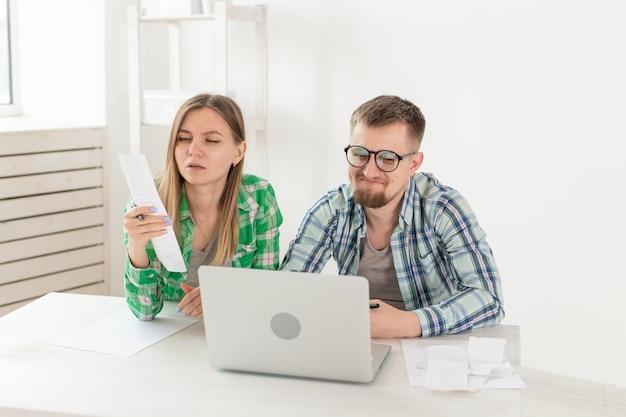 Удивленная семейная пара. муж и жена рассматривают счета на оплату квартиры и