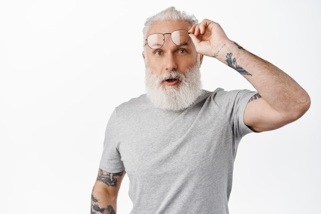 Surprised mature guy with long beard, take-off glasses and look in awe, staring at something amazing, standing in grey t-shirt against white wall