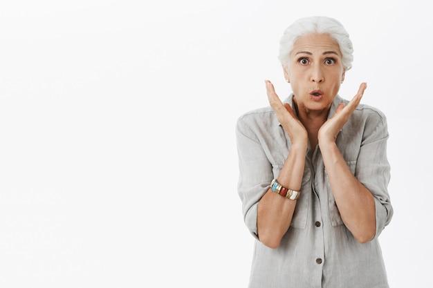 Удивленная зрелая женщина с седыми волосами выглядит удивленно, реагирует на потрясающие новости