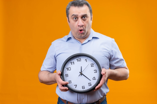 Surprised middle age man in blue striped shirt holding wall clock showing time on an orange background