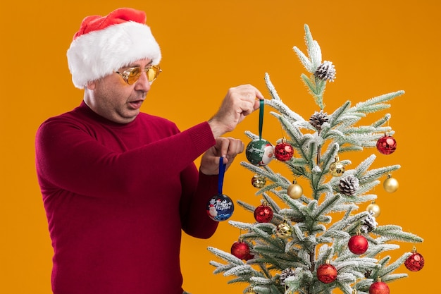 Удивленный мужчина средних лет в новогодней шапке санта-клауса в темно-красной водолазке и желтых очках украшает елку, стоящую над оранжевой стеной