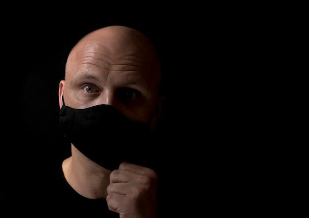 黒の背景にcovid19黒の医療マスクを脱いで驚いた中年の白頭ワシ